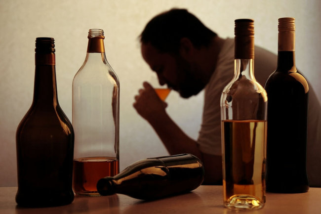 man drinking with a bunch of bottles, how much alcohol is too much
