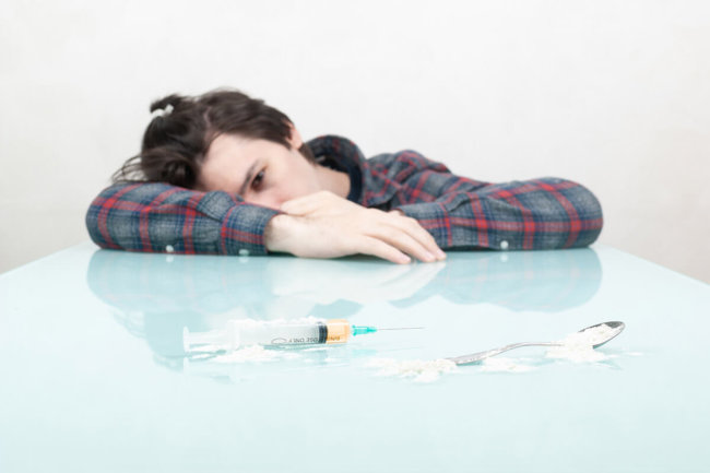 man slumped on table with needles, signs of heroin use
