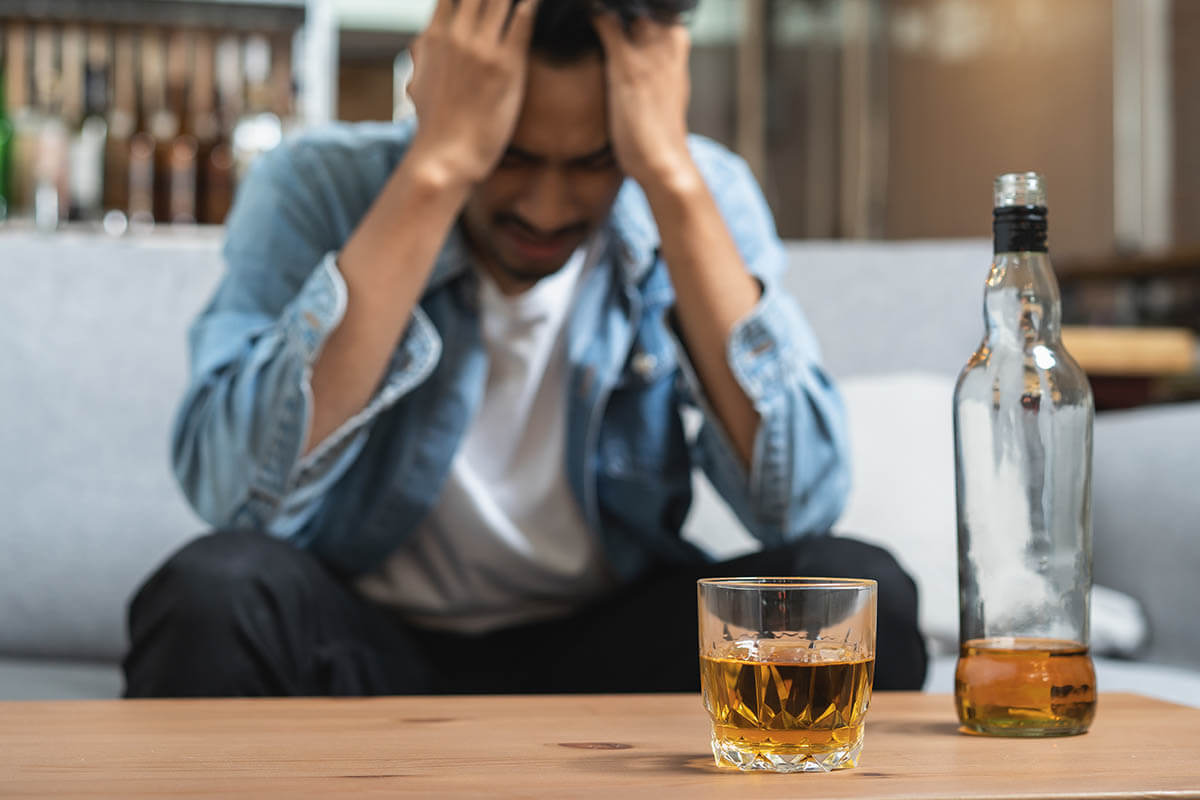 man with hands to face with alcohol on table, is alcohol a drug