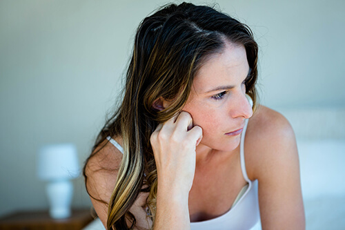 A woman looks concerned while worrying about the addiction recovery process.