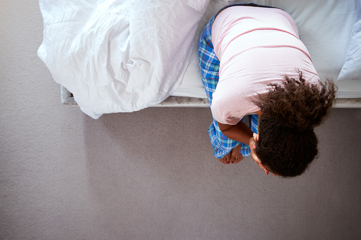 woman getting out of bed holding head from different Types of Addiction issues