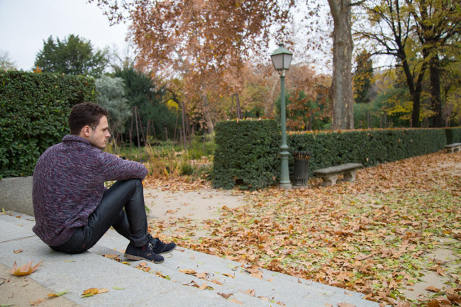 man sitting on steps alone wondering how to overcome addiction