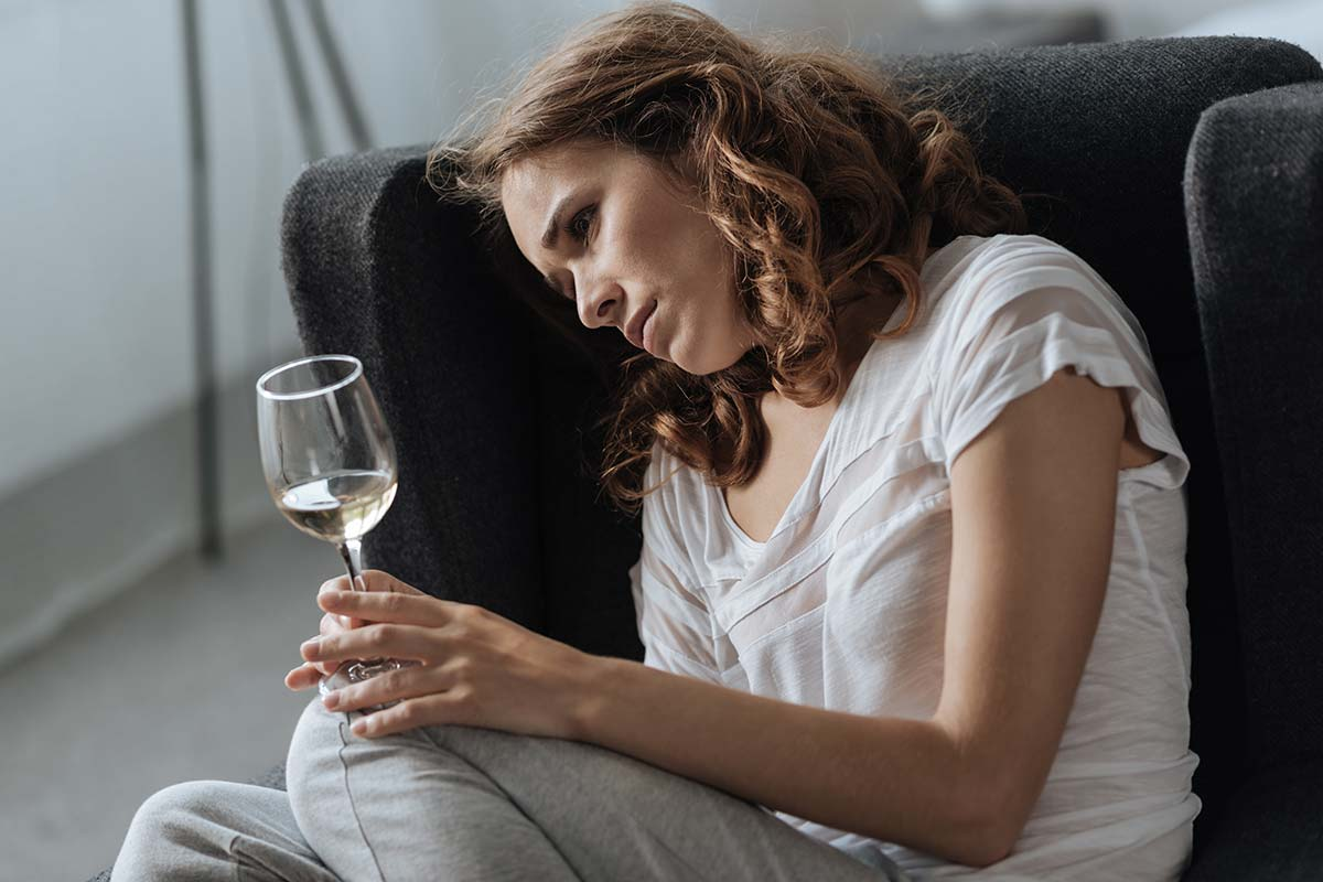 pensive woman drinking white wine, depression and alcohol
