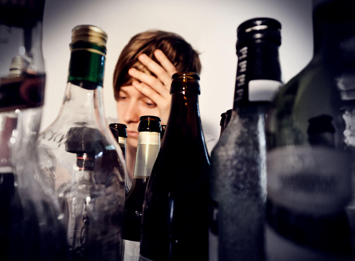 androgynous person surrounded by empty bottles of alcohol suffering from alcohol withdrawal