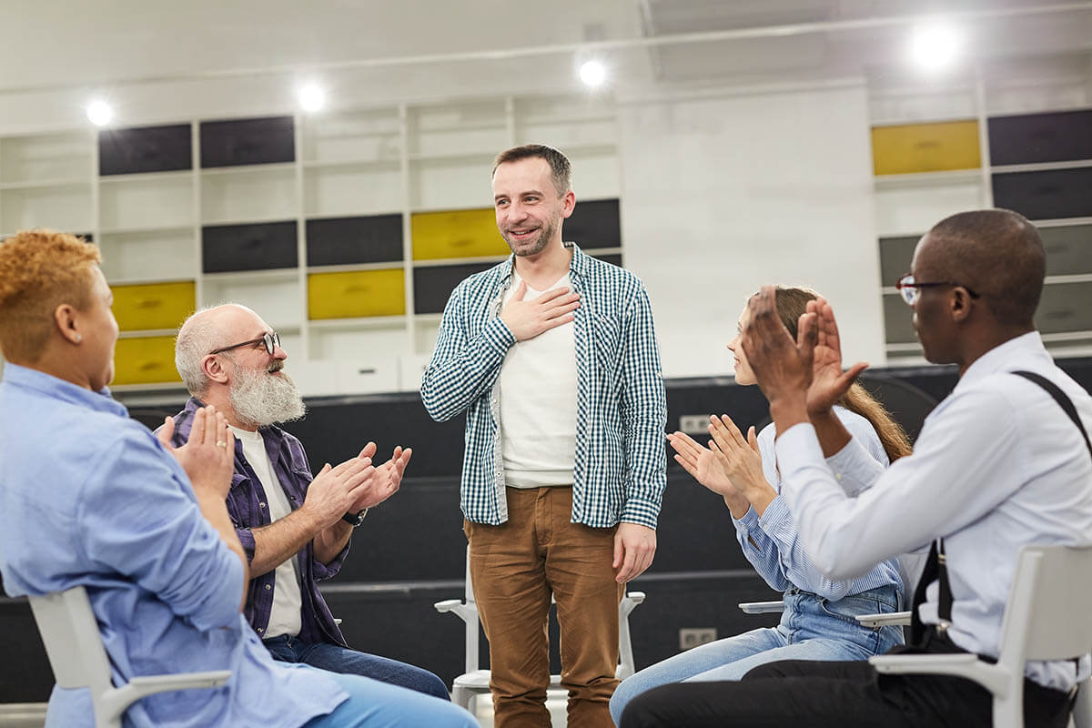 man standing up in front of supportive therapy circle is what is an aa meeting like
