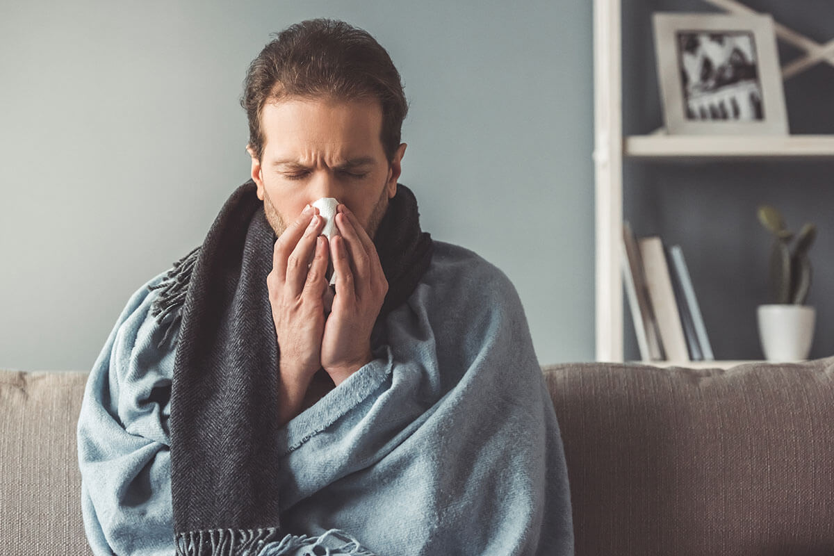 sneezing man on couch worried about addiction and your physical health